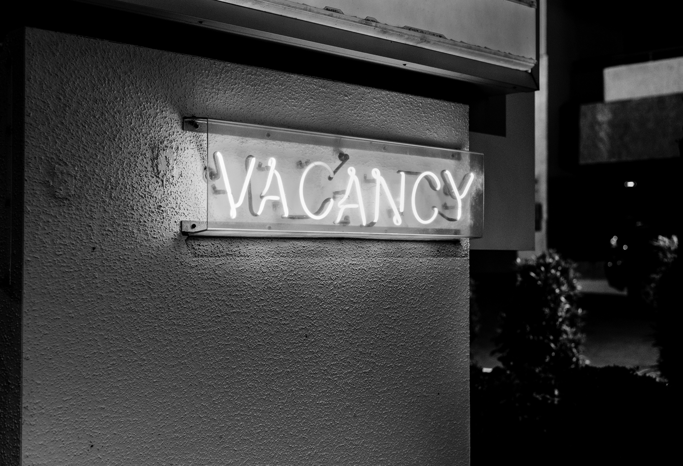 A lit-up neon Vacancy sign attached to the side of a building