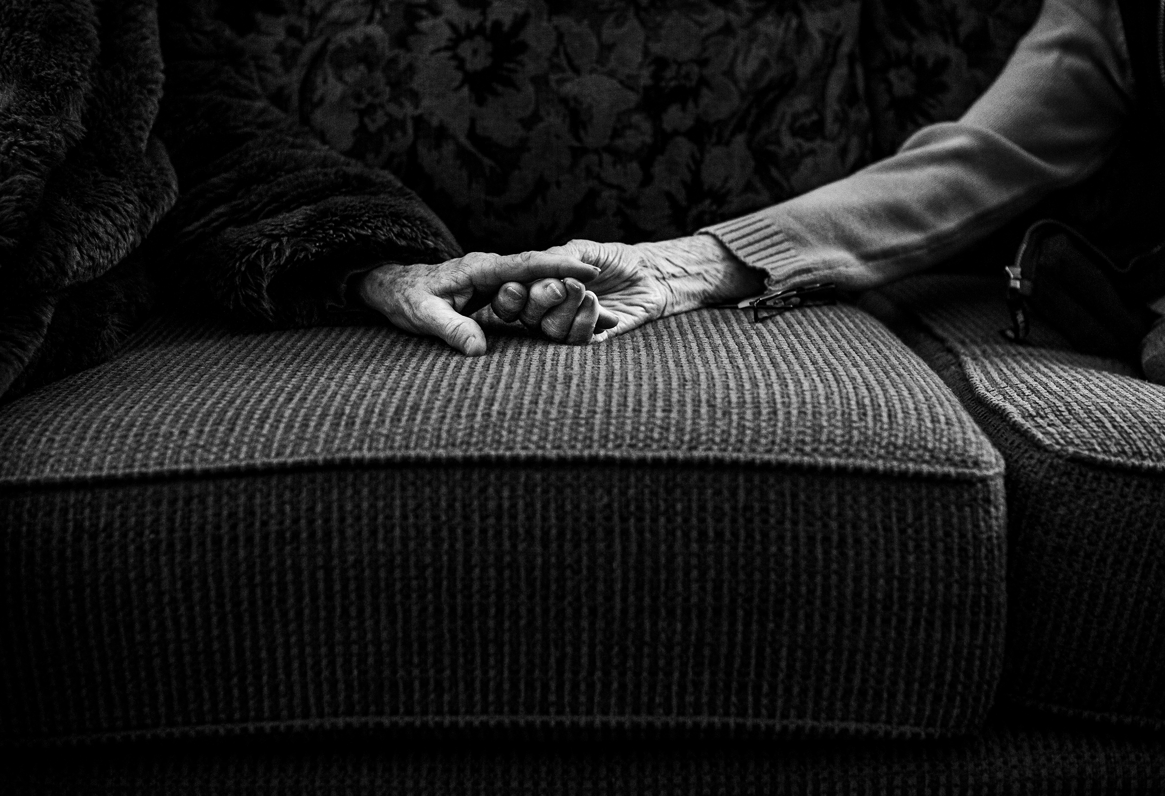Two elderly people holding hands on a sofa with a close-up on the hands.