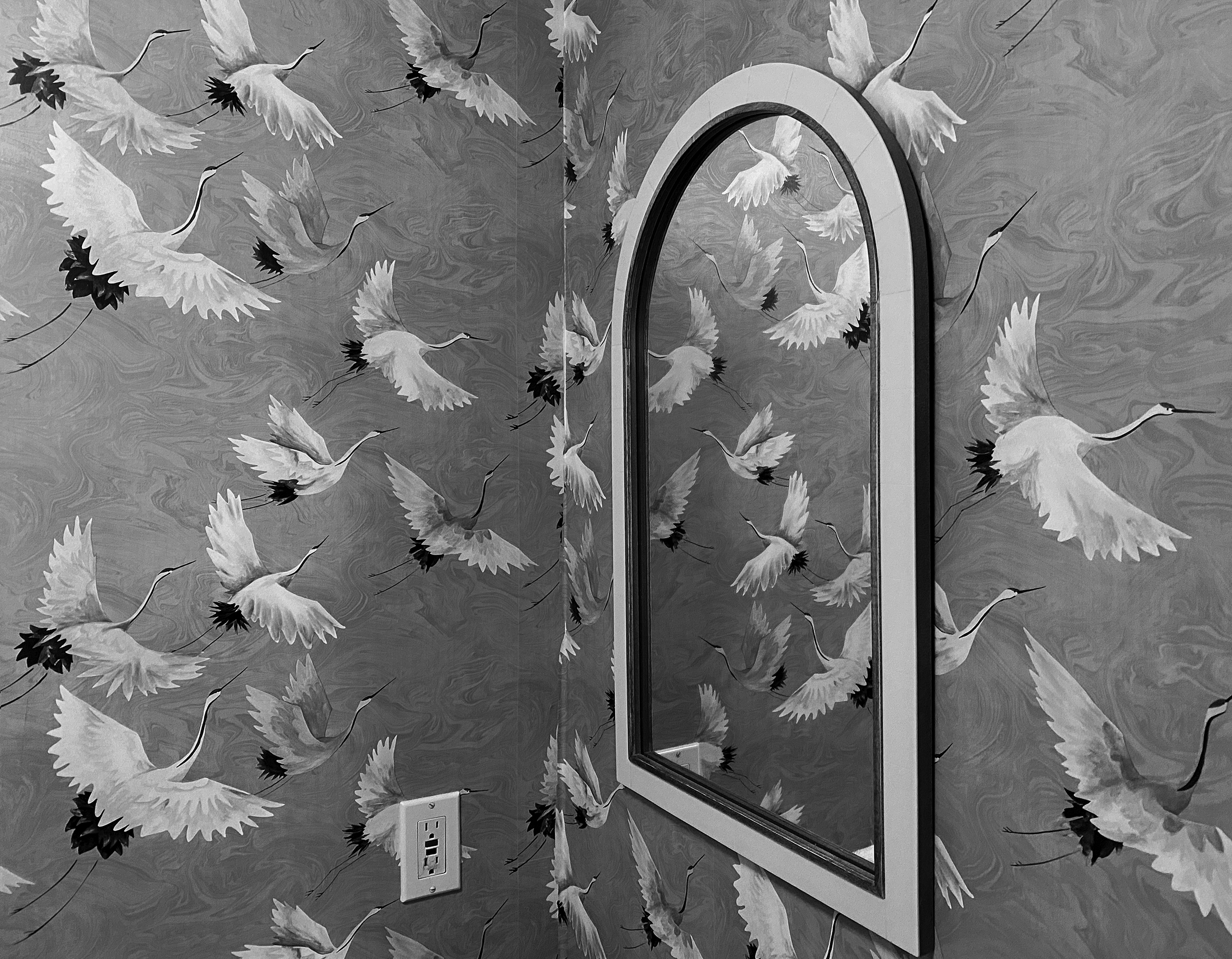An arched mirror next to a corner with wallpaper full of flying cranes.