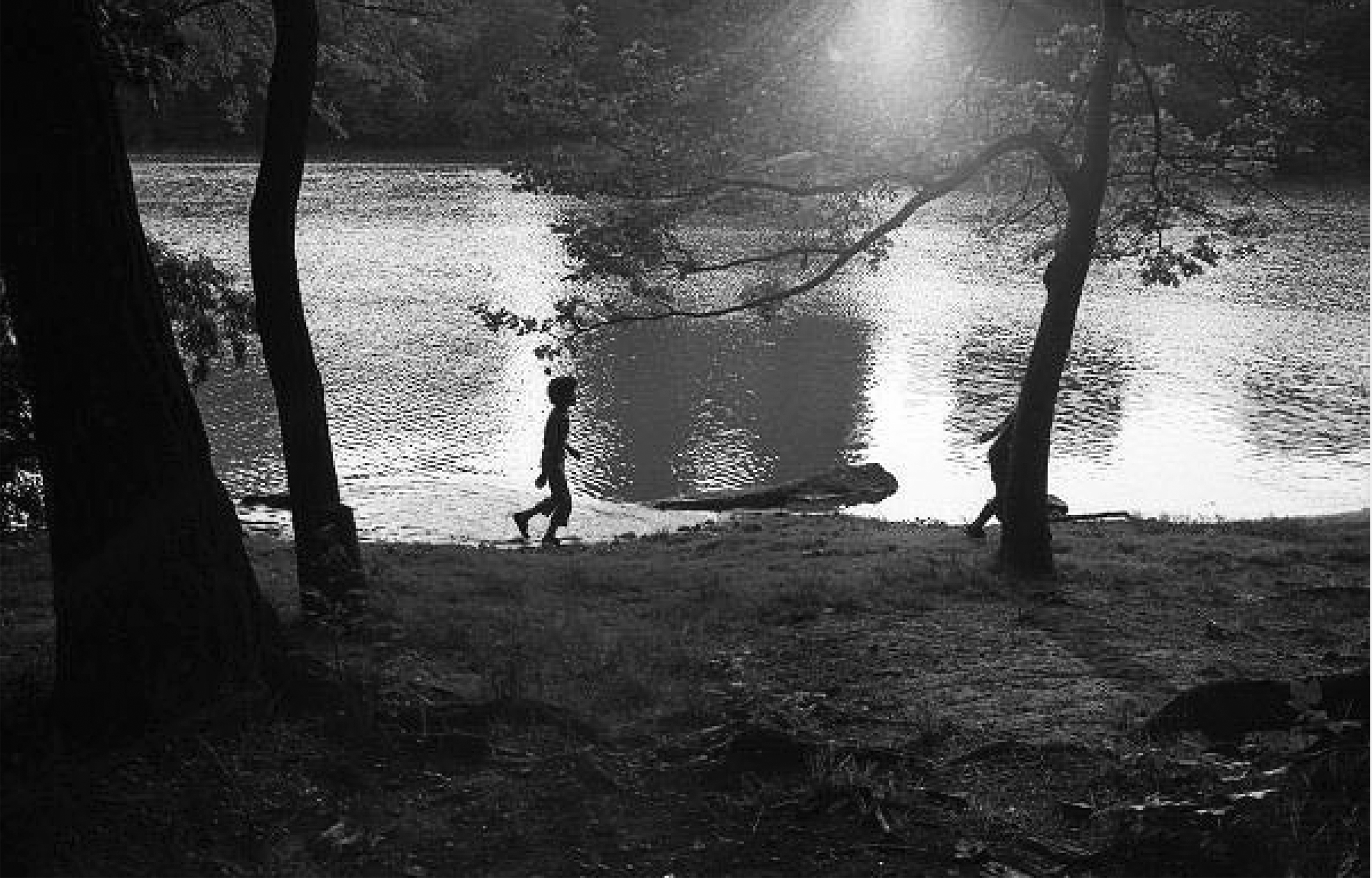 The silhouettes of two children as they walk along a lakeshore.