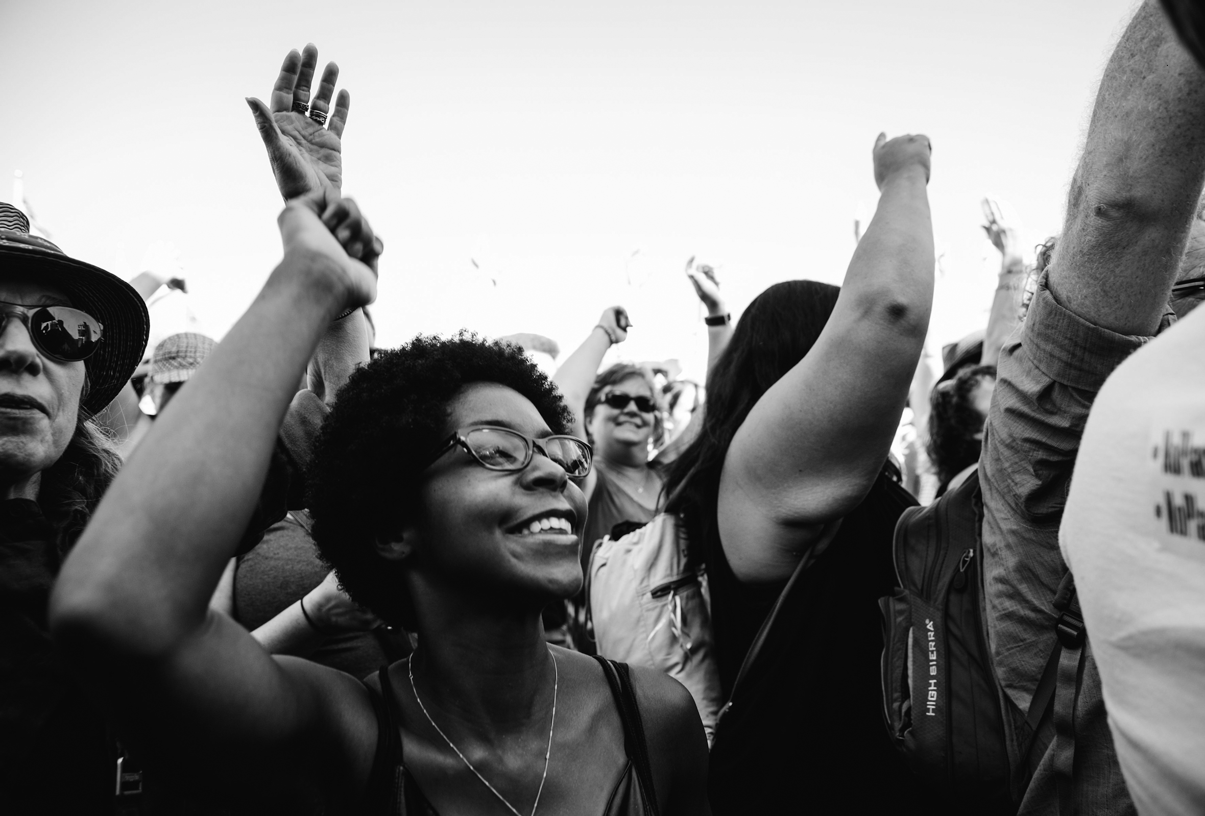 A Black woman, smiling, throwing her hand up in the air among a diverse crowd of protesters.