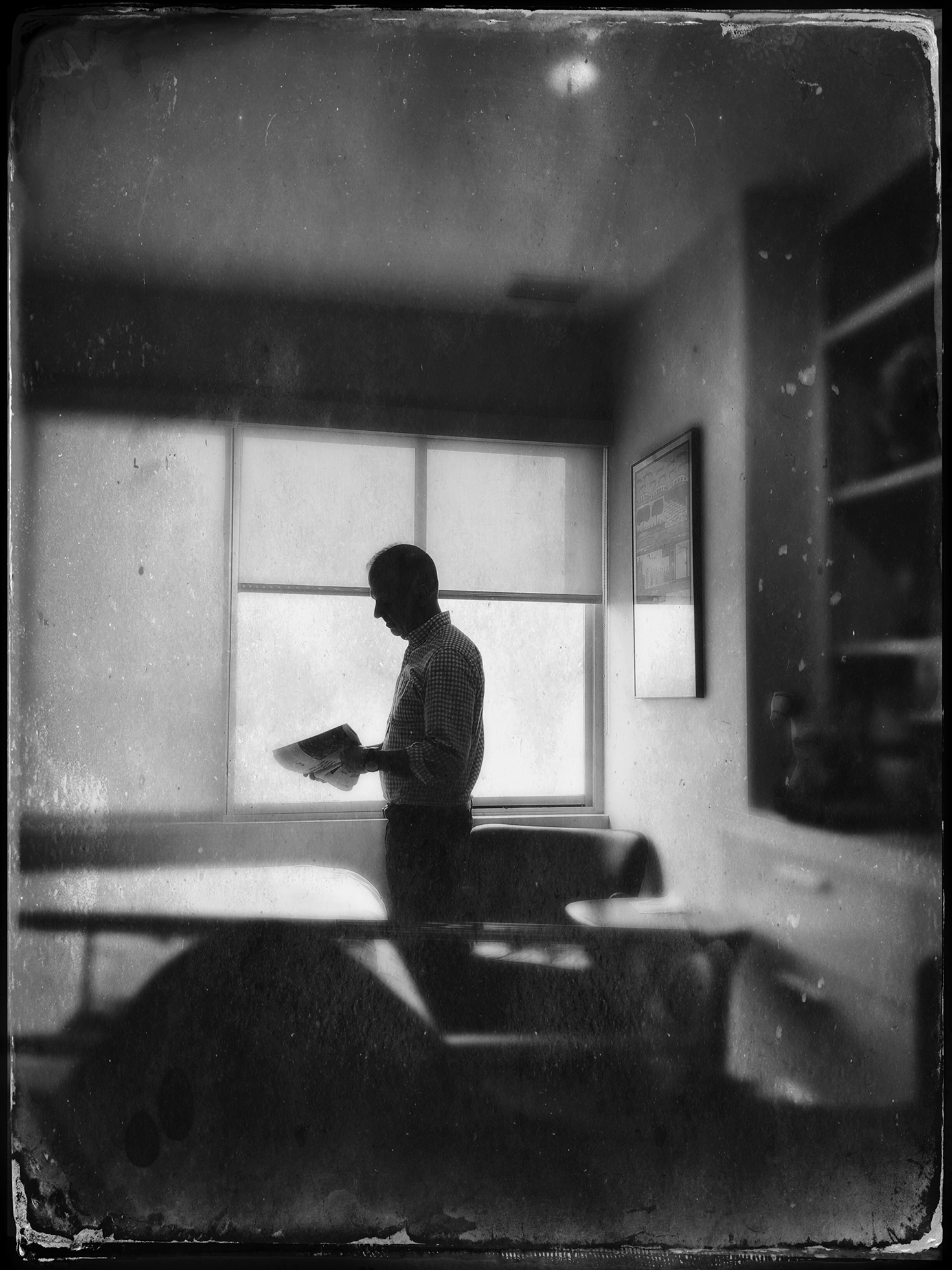 A male teacher stands silhouetted against the window of an empty classroom. He is looking down at papers in his hands.
