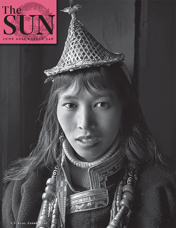 A portrait of a woman from Bhutan who is dressed in her regional wear including a triangular hat.