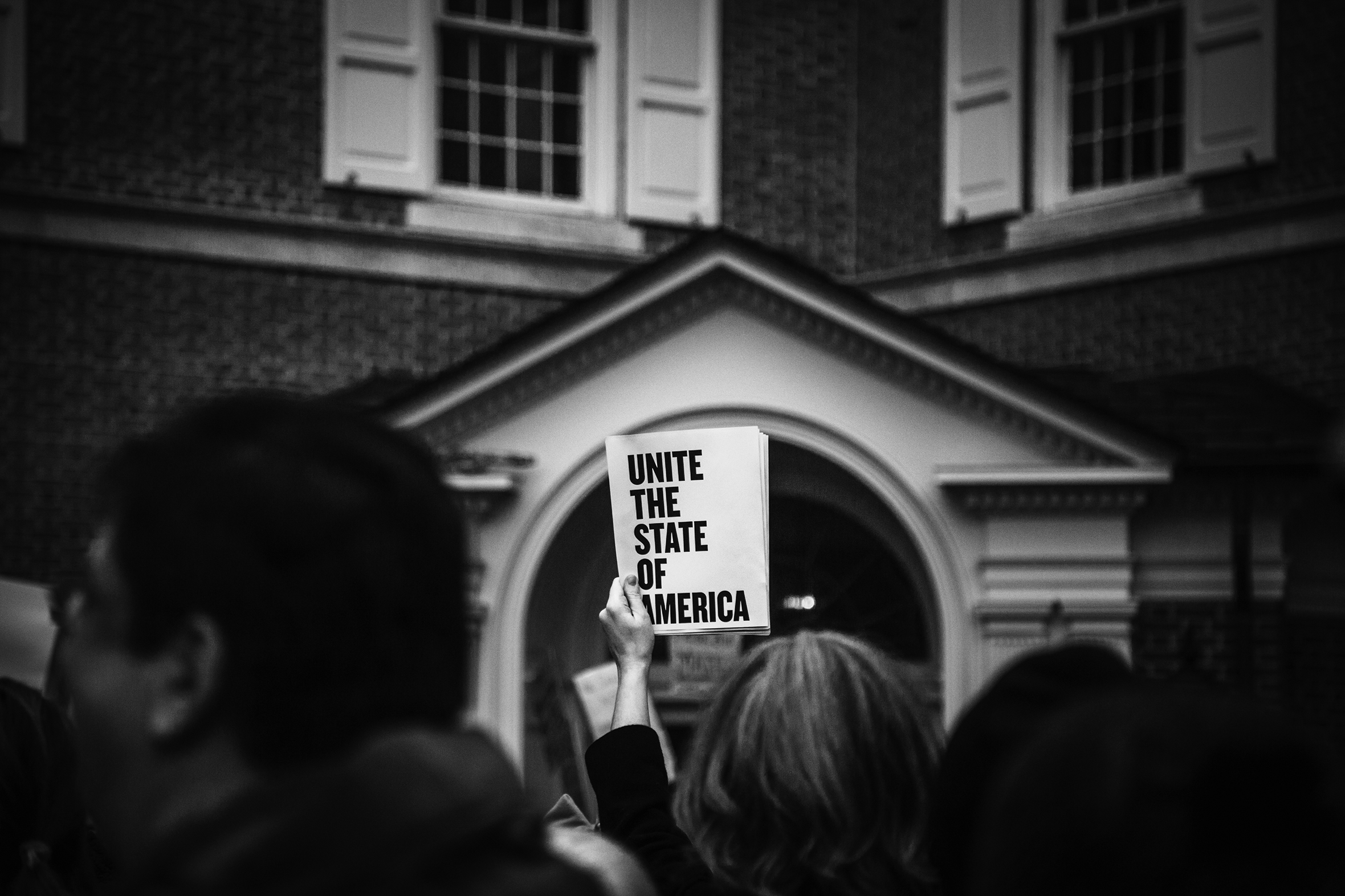 A crowd of protestors is in front of a building. The camera is focused on one sign that stands out and says Unite The State Of America.