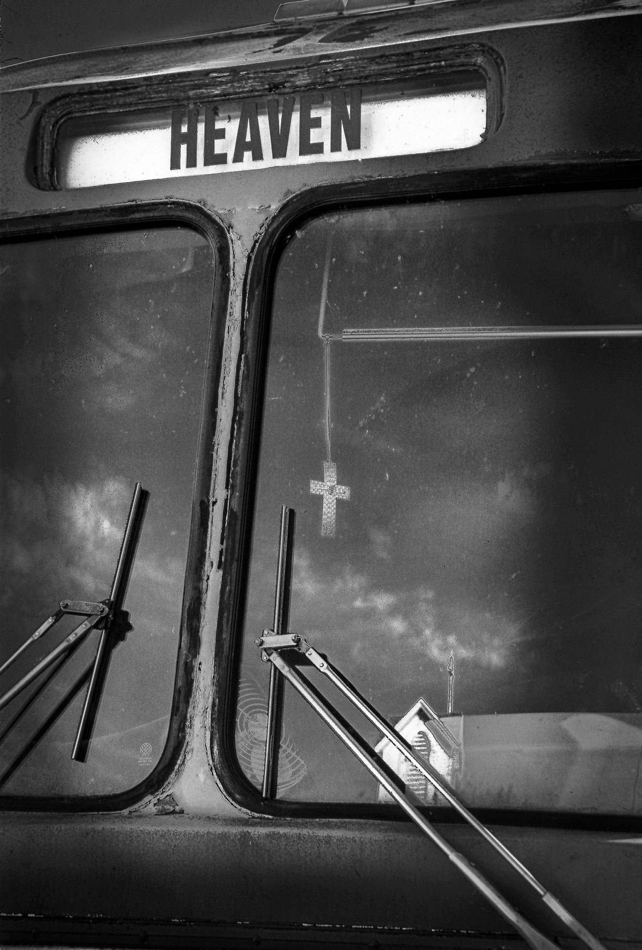 A bus with a destination sign  that says HEAVEN. A church can be seen in the reflection of the windshield.