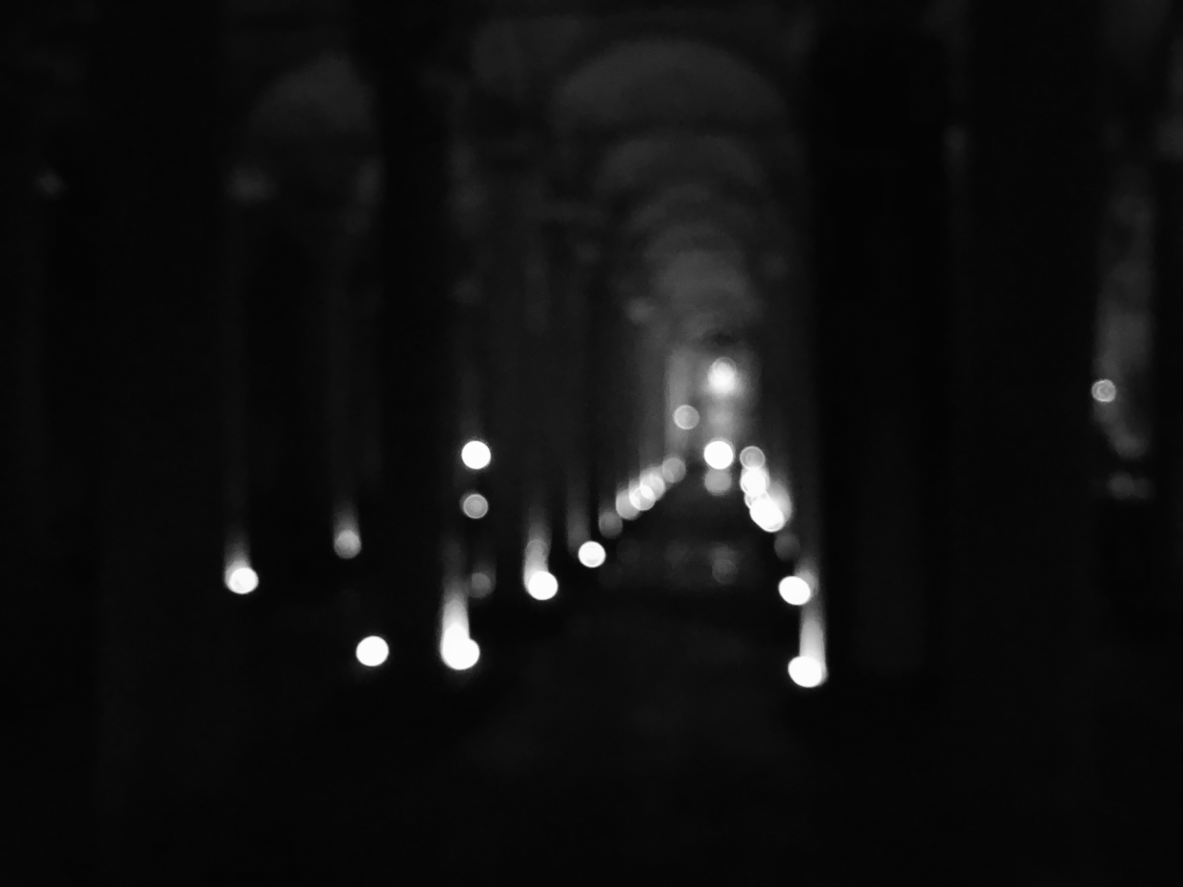 A blurry photo of what appears to be lights on either side of an aisle.
