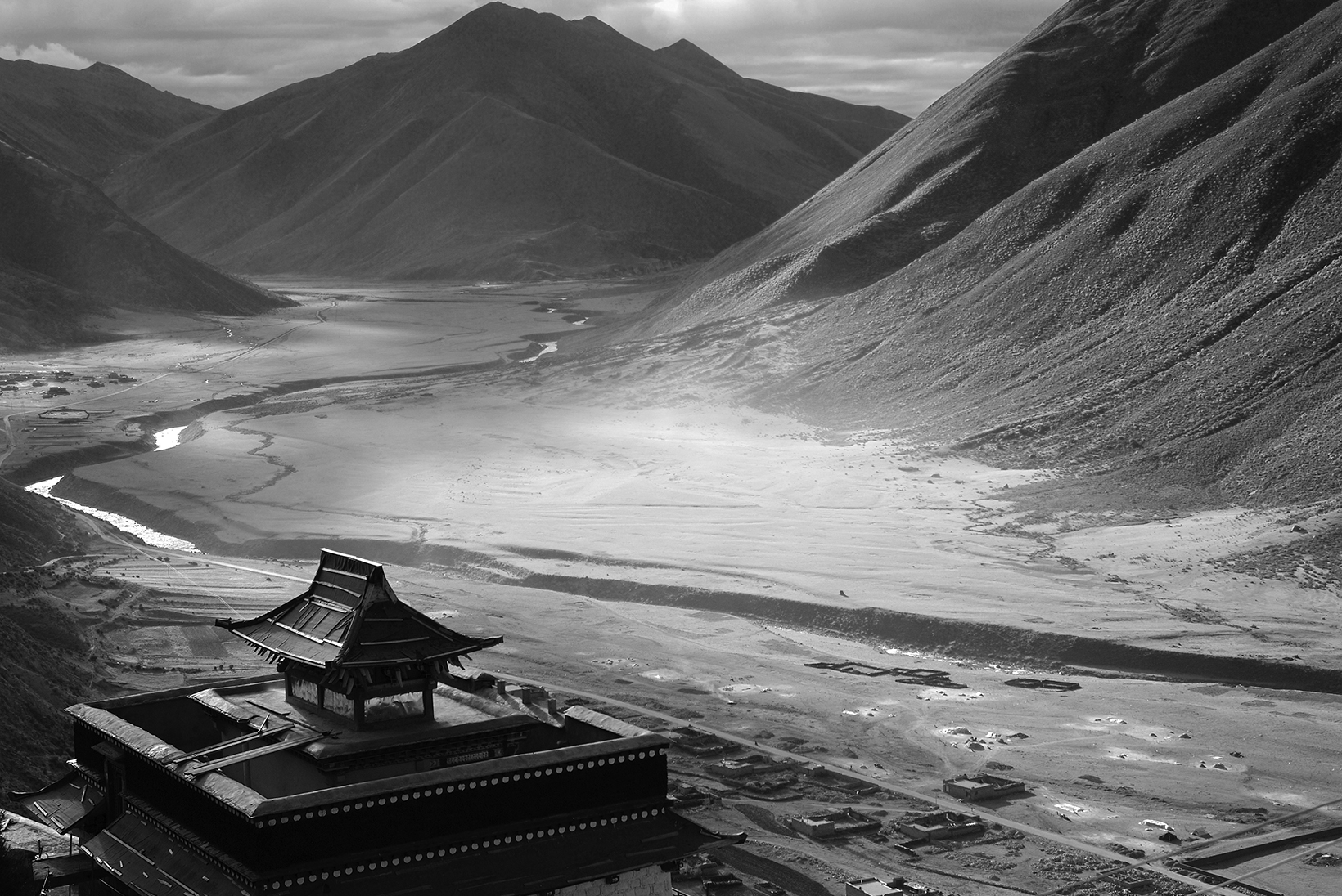A landscape shot of a valley. Mountains are off in the distance. A river cuts through the middle. In the foreground, along the left corner is a Buddhist temple.