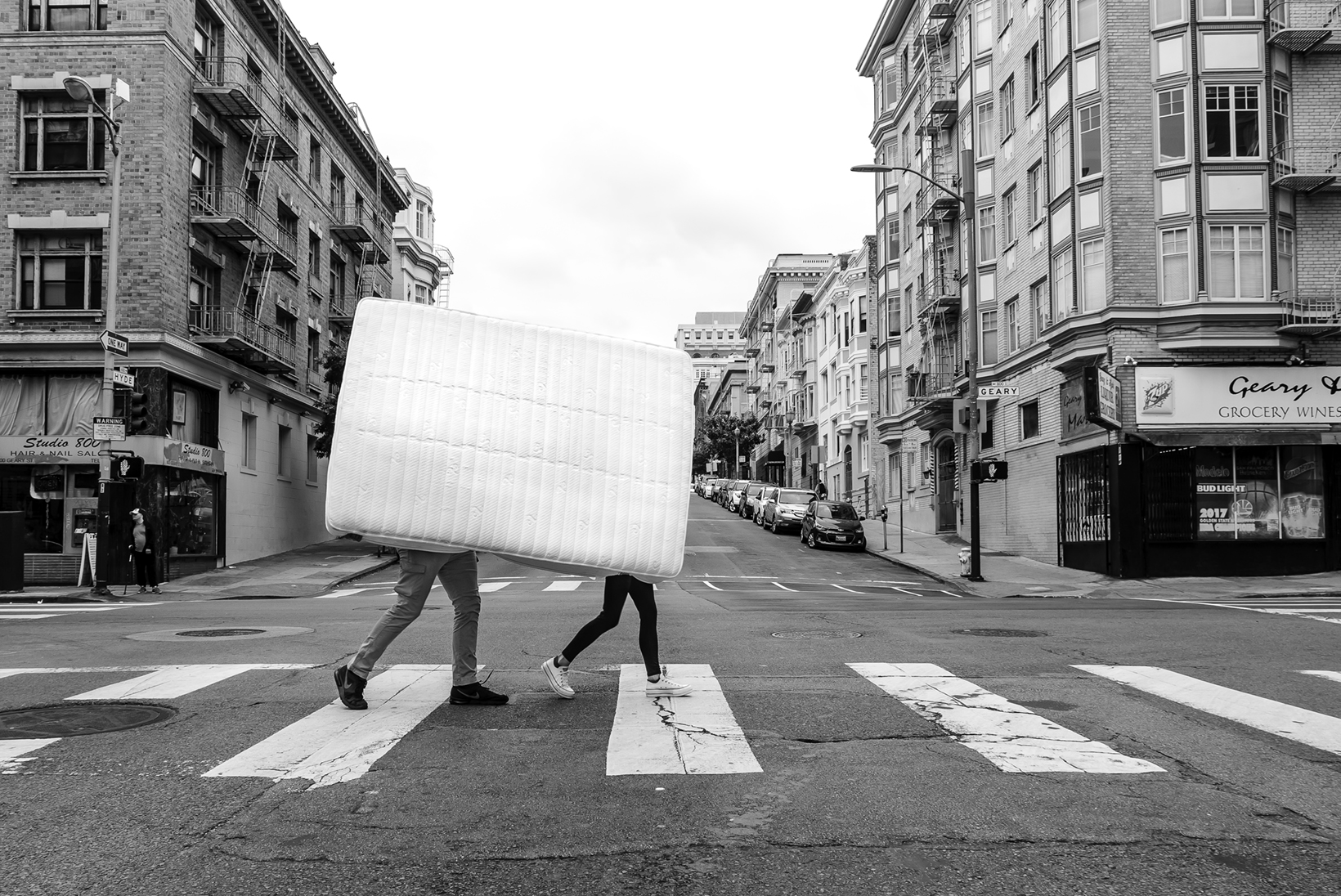 Two people, who are obstructed by the mattress they are carrying, walk in a crosswalk in a city.