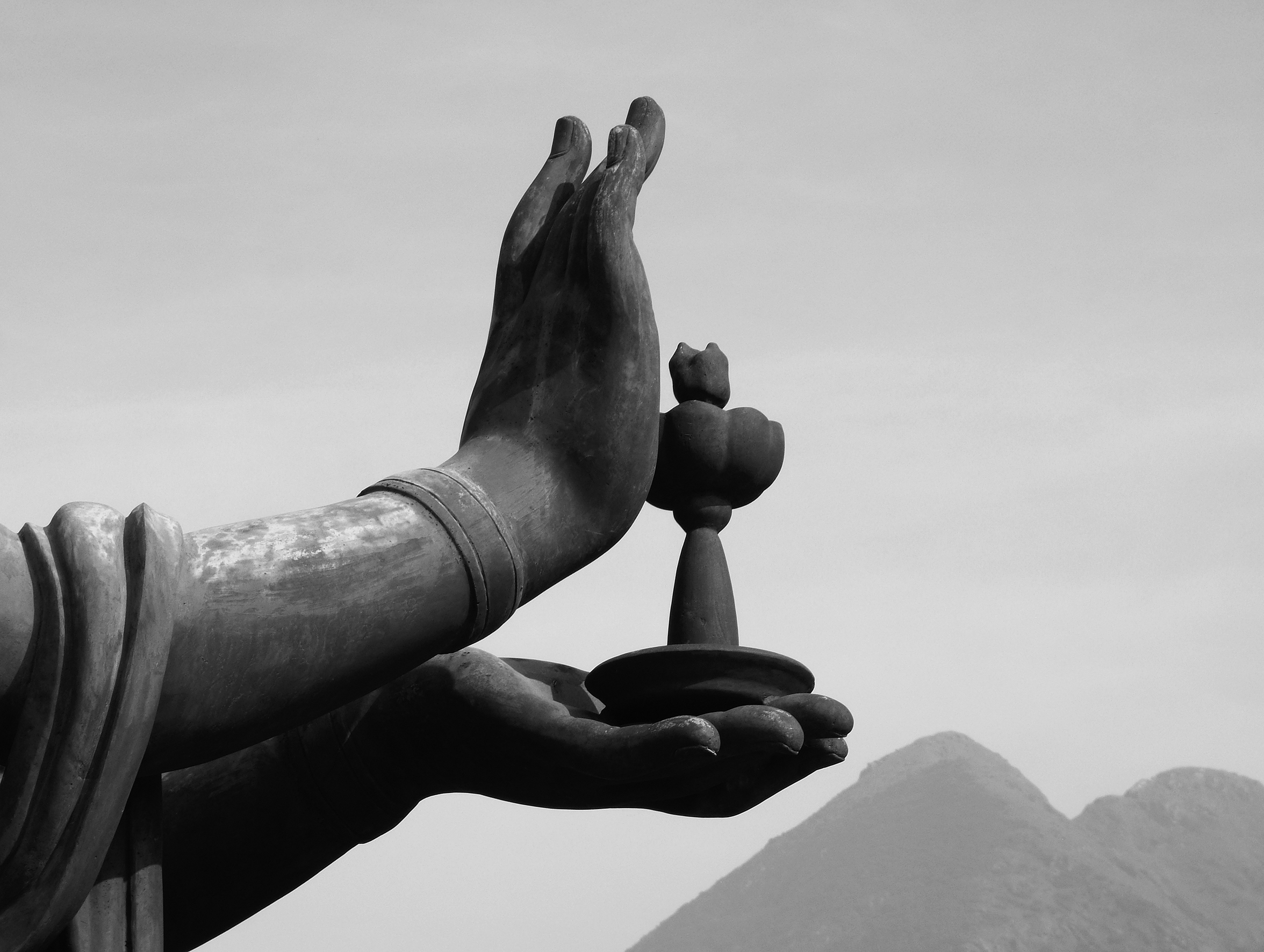 A close-up of a statue's hands holding what appears to be a lotus. Mountaintops are just peeking from the bottom-right corner of the image.