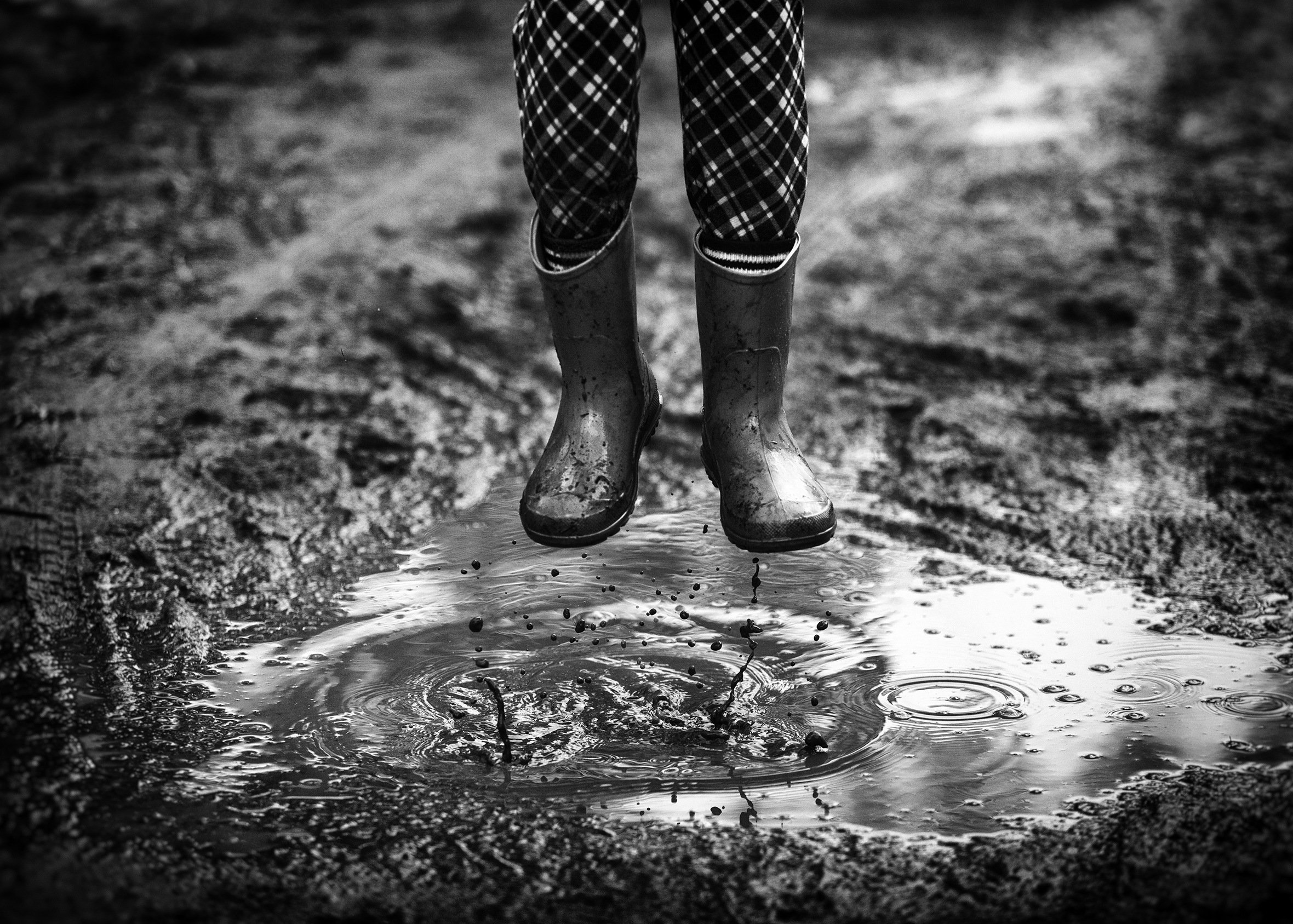 A close-up of a child's legs with the pants tucked into rain boots taken mid-jump over a mud puddle.