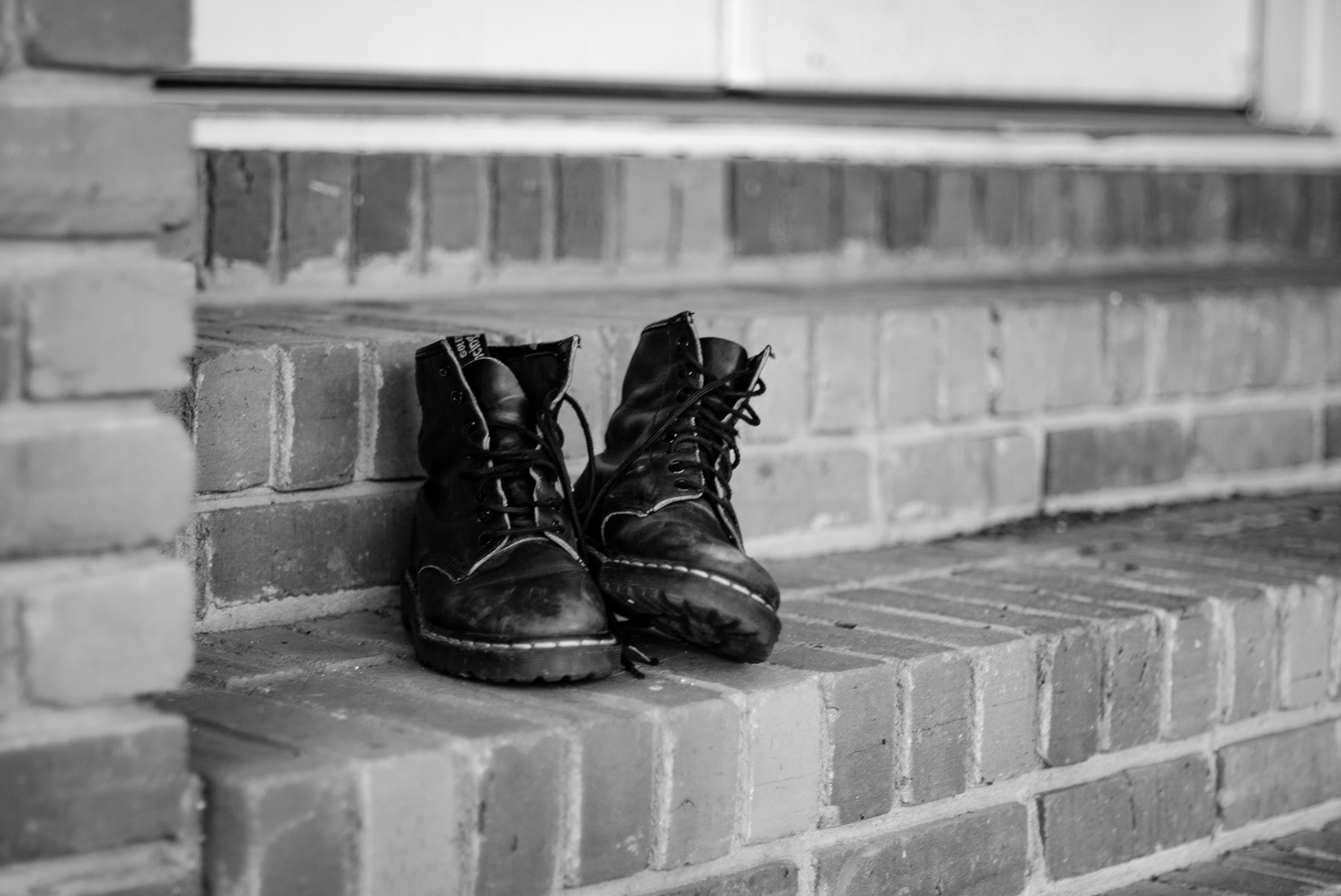 A close-up of black boots upon a brick step outside a door.