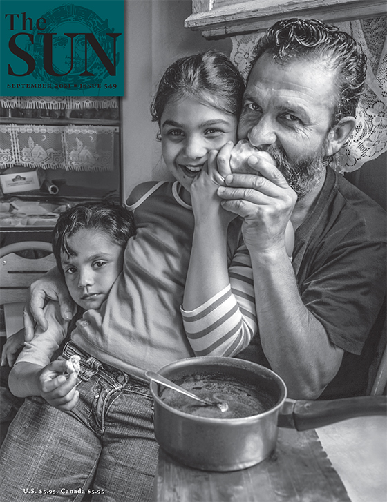 A Romani family. The father is sitting and taking a bite of an apple while his daughter sits on his lap and holds a part of the apple. Another child leans in close to his sister with the father's other hand seen embracing the second child's shoulder.