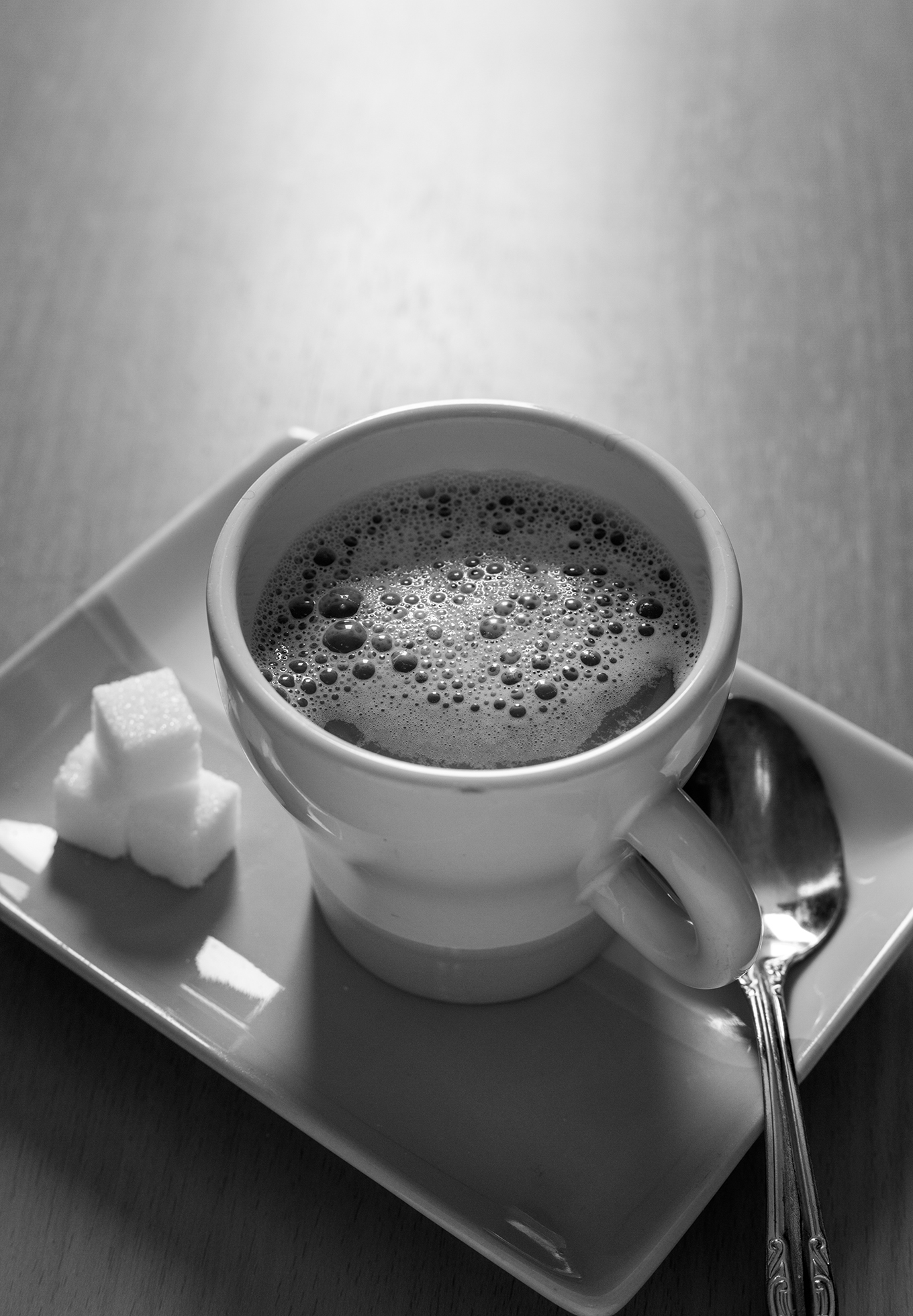 A close-up of a cup of coffee on a rectangular serving plate. Three cubes of sugar are stacked to the left of the cup and a teaspoon is placed to the right.