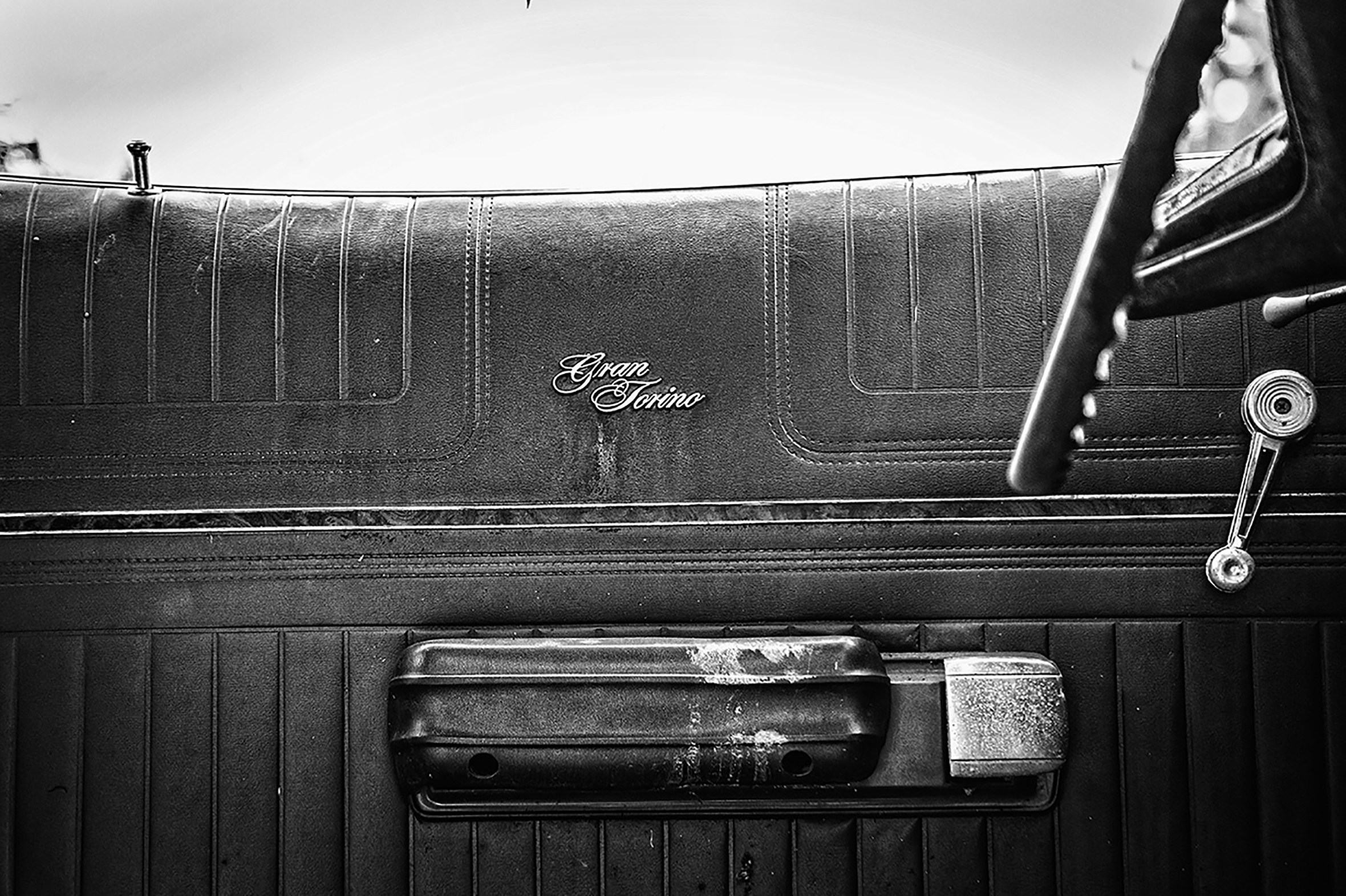 A close-up of the inside door of a Gran Torino. The steering wheel is just visible. The latch of the door is slightly worn.