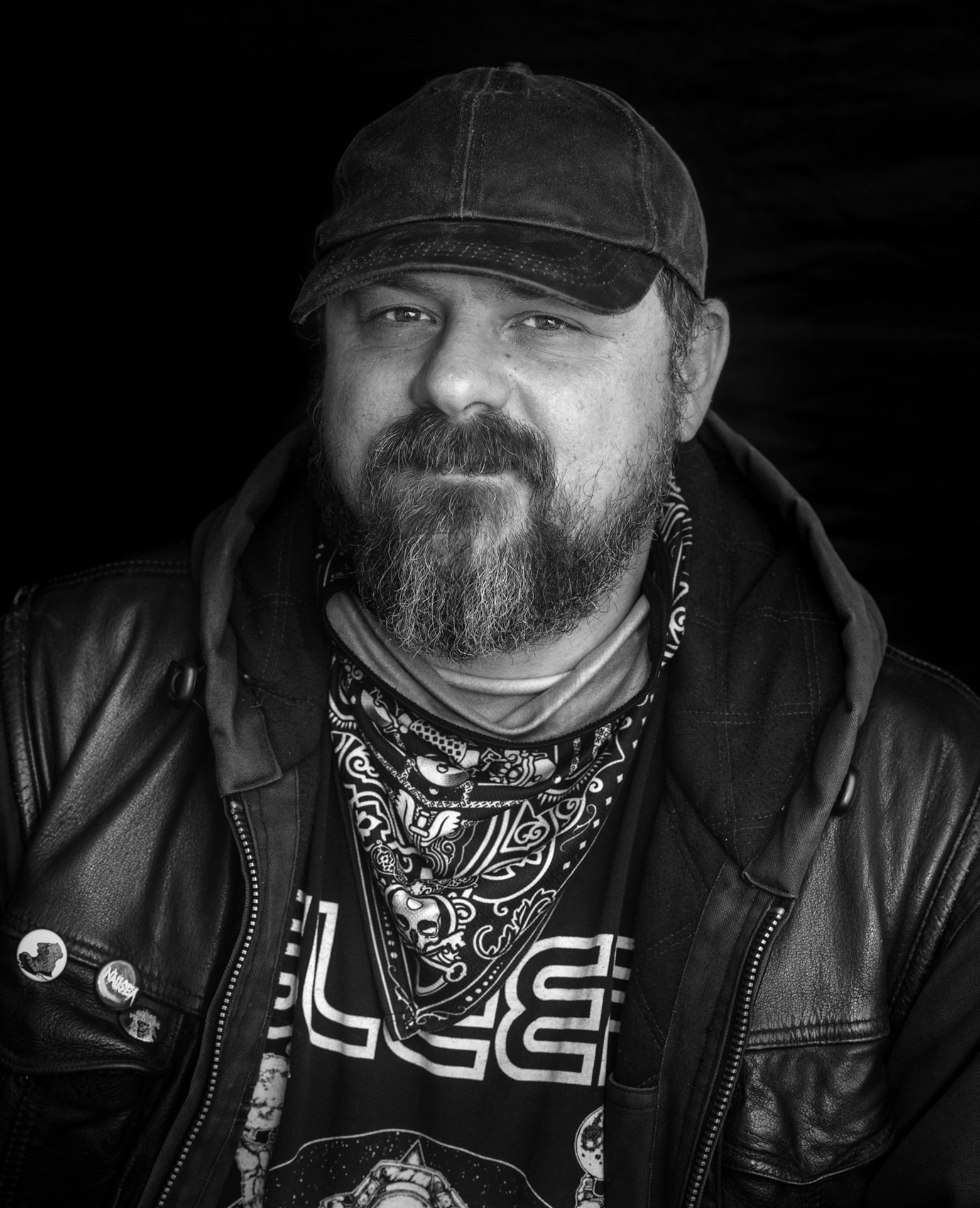 Graham Pruss wearing a black leather jacket. A handkerchief is around his neck and he's wearing a dark denim ball cap.