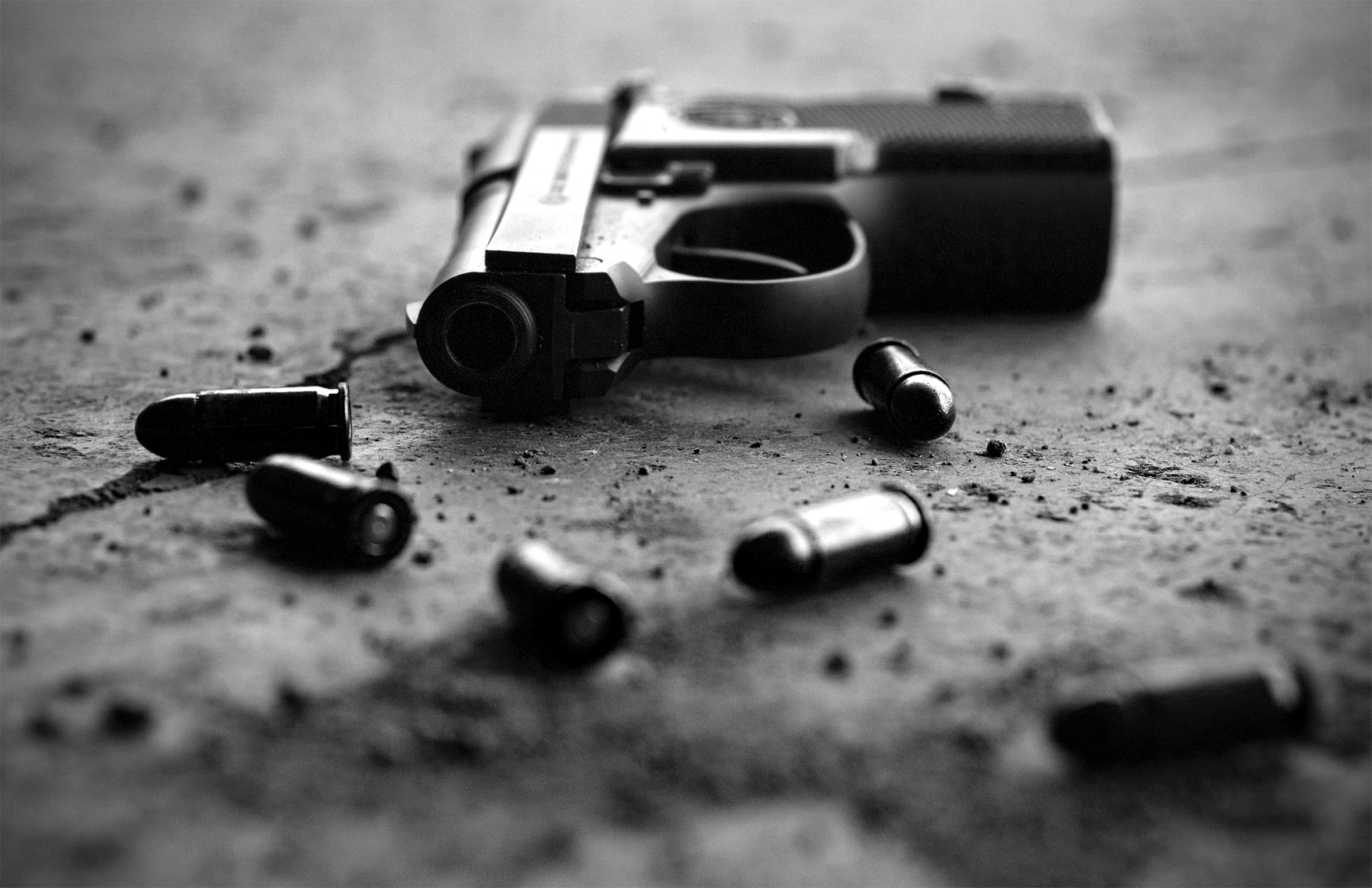 A close-up of a pistol and six bullets lying on the ground. The barrel of the pistol is pointed toward the camera.