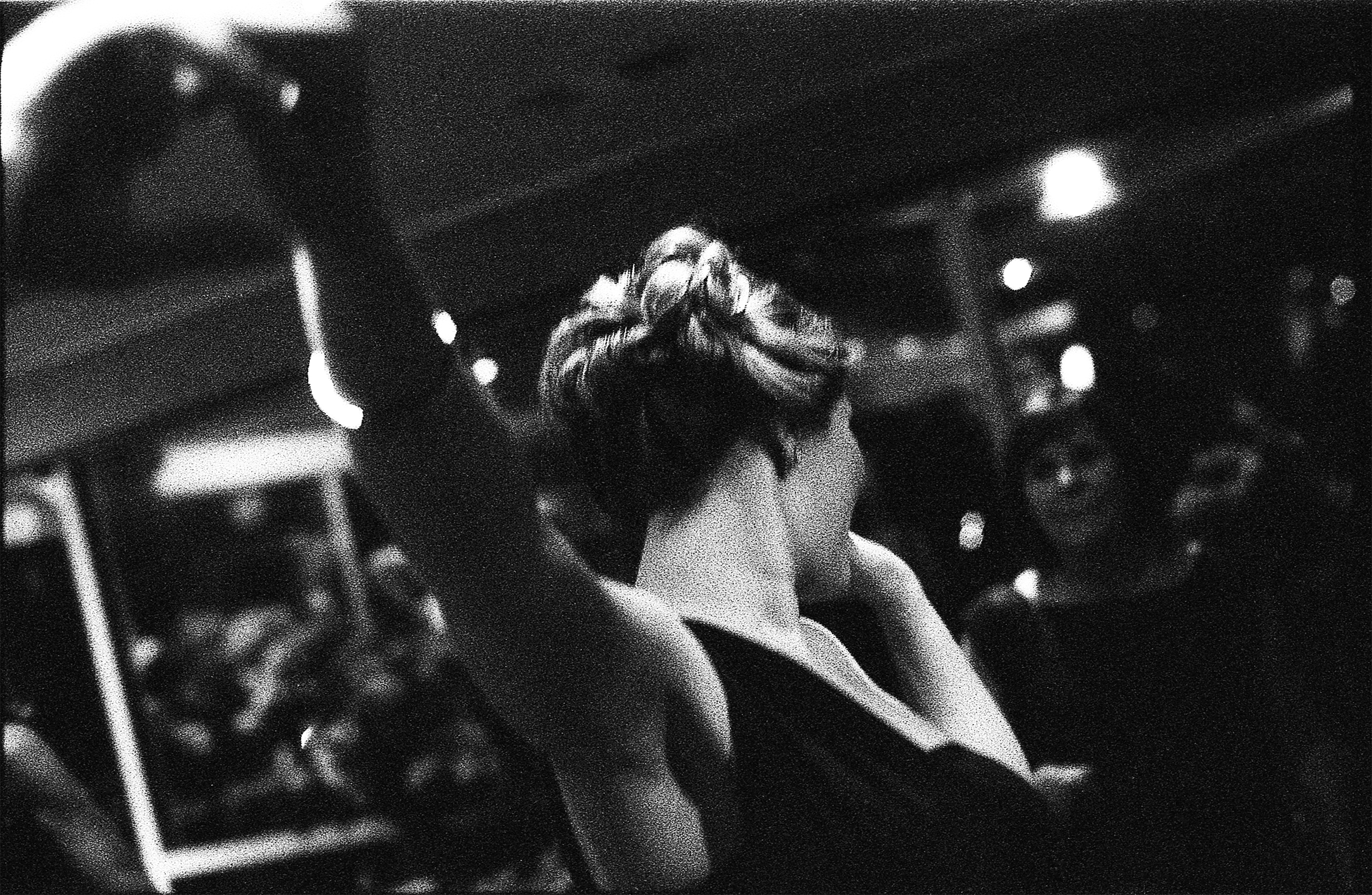 A woman with an elegant, updo hairstyle is facing away from the camera. She appears to be dancing in a darkened room. The shadows of people can just be seen around the edges.