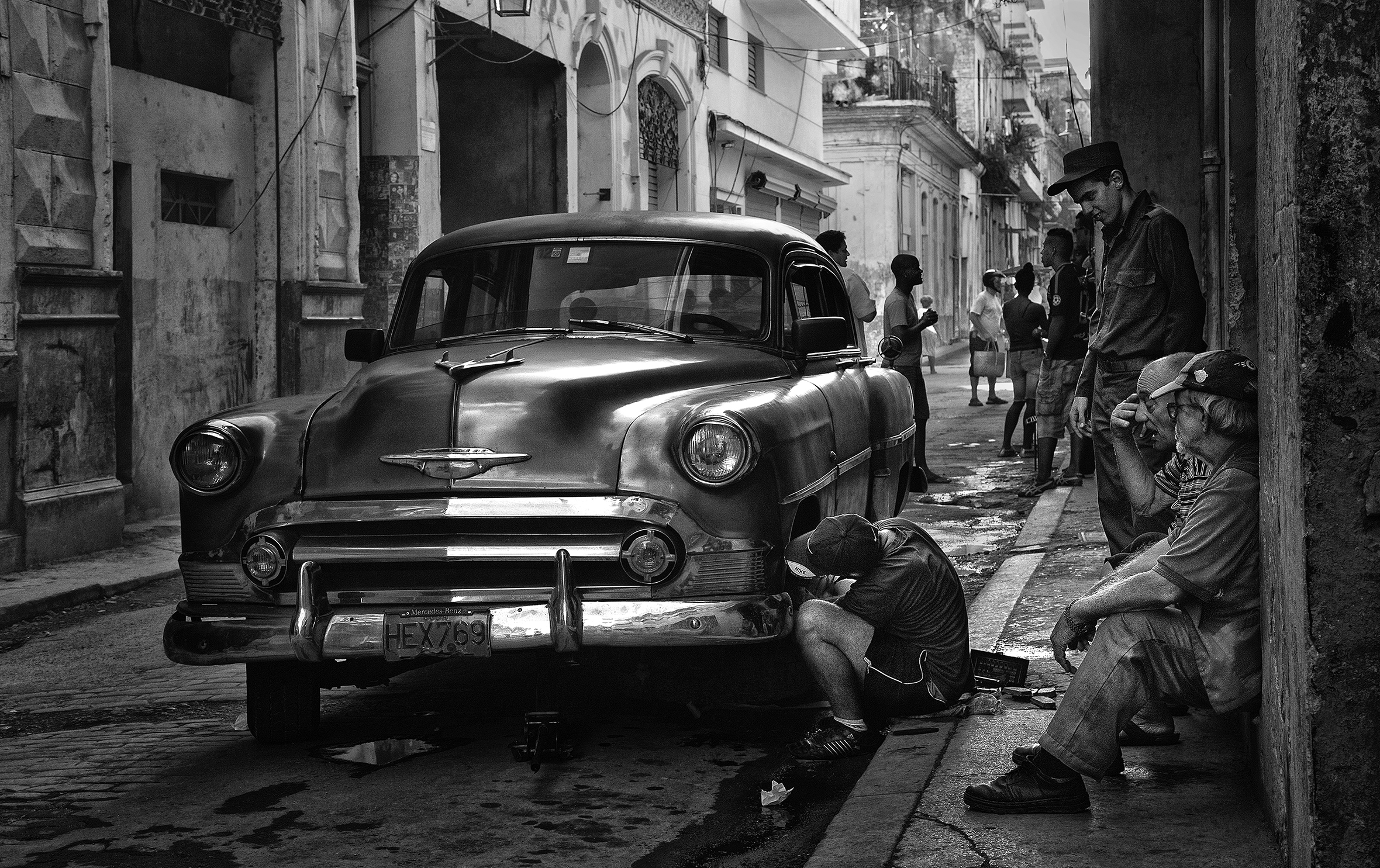 A young man is working on a vintage car with a Cuban license plate parked on the street. A couple of old men are watching from the sidewalk as people go about their daily lives in the background.