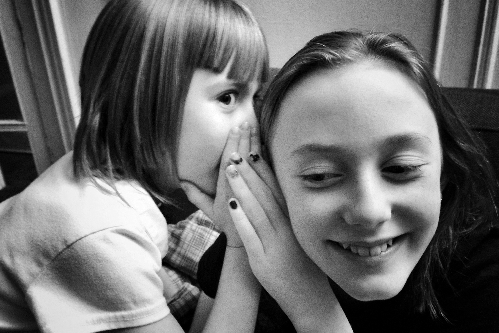 A young girl whispers in a teen girl's ear. The teen girl listens closely and smiles.