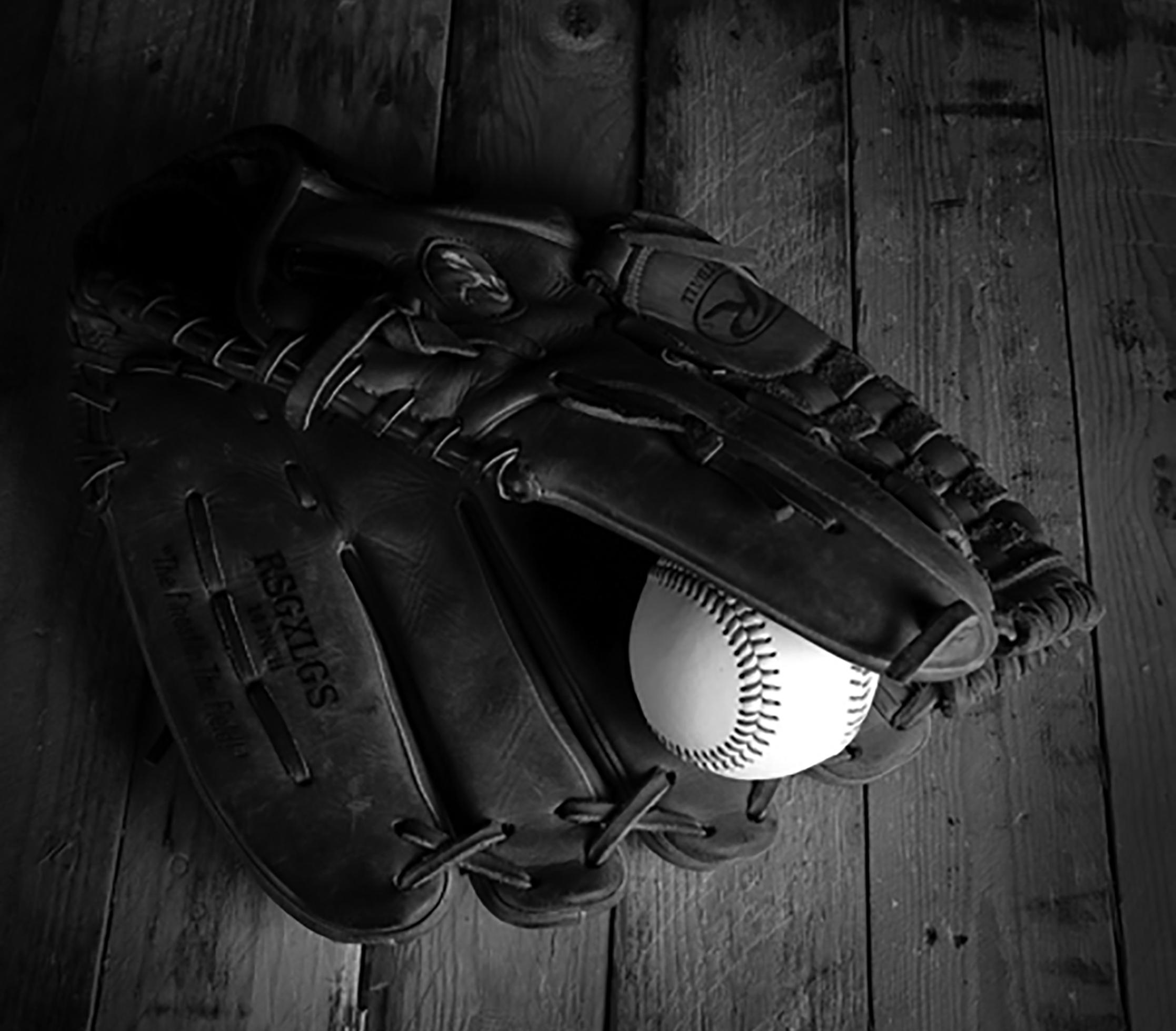 A close-up of a baseball glove on a wooden floor. A baseball is seen peeking inside the glove.